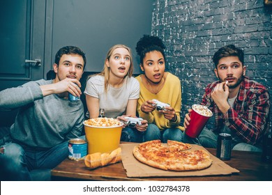 A small company sitting together where boys are drinking some coke while girls are playing the game. The game is very intense. Gamers. Night party.