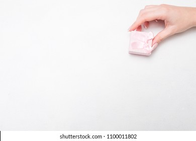 small compliment feminine present on anniversary birthday or valentines day. woman hand holding tiny precious gift in a jewelry box on white background. free space concept