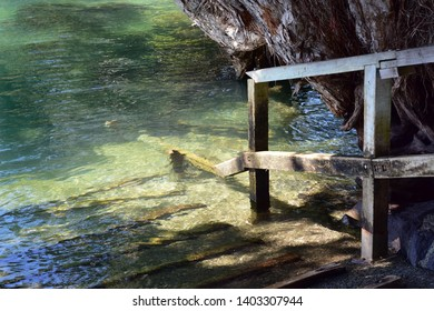 Small concrete boat ramp for dinghies with timber railing partially submerged at high tide.