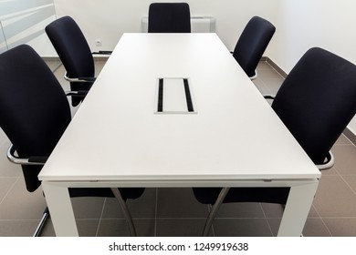 small conference room, white table and black chairs