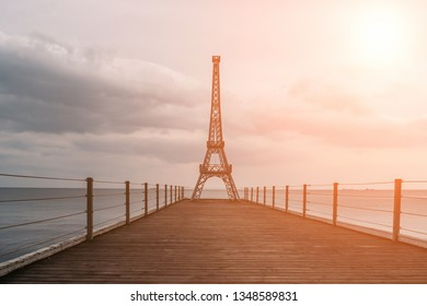 Small copy of famous Eiffel Tower on end of pier in Yalta, Crimea at sunset, copy space