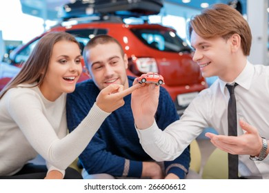 Small copy of your babe. Joyful salesman holds a toy model car showing it to the customers who touch it with the finger with blurred showroom view on the background