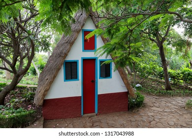 Small cosy chalet with a triangular thatched roof in between of green trees. Portuguese island of Madeira