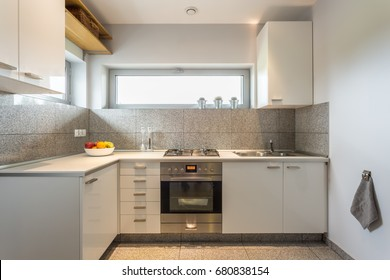 Small but cosy kitchen with window and white walls
