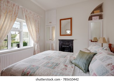 Small cottage bedroom with antique cast iron fireplace, built in cupboards, mirror and bed taking up most of the room
