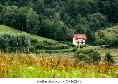 A small cottage with red roof between greenery