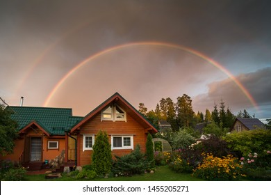 Small country house on a summer evening. Rainbow over the house. Beautiful sunset. Flowers in the garden. Russia