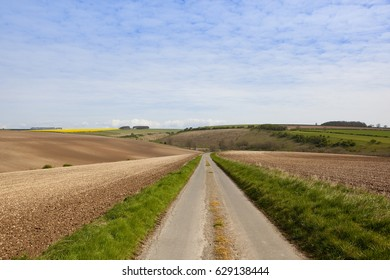 a small country road going through undulating agricultural scenery in the yorkshire wolds under a blue cloudy sky in springtime