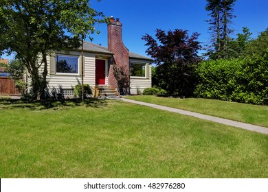 Small countryside house exterior with siding and brick trim. Northwest, USA