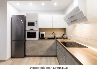 Small cozy kitchen in modern apartment. New kitchen with modern appliances. Kitchen with wooden countertop.