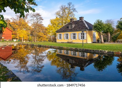 Small cozy old house of the past centuries with 4 windows and a tiled roof. A yellow house in the countryside is reflected in the water on a sunny autumn day. Country villa cottage in vintage style.
