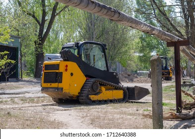 Small crawler excavator with rubber tracks. Yellow skid steer loader at a city street working with a soil. Industrial machinery. Industry.