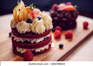 Small cream cake wit berries and physalis decoration on wooden plate