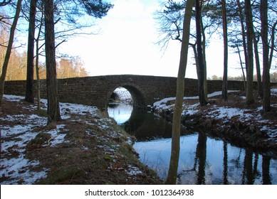 Small creek with an ancient stone bridge at the swedish island Oland