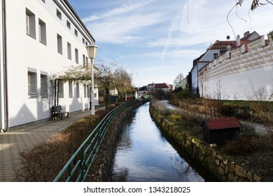 The small Creek running through Trebon Town, in Southern Czech Republic, with the typical white buildings on each side, and blue autumn sky and sunshine.