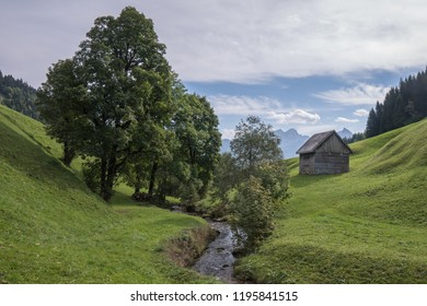 Small creek in the Swiss Alps in the Canton Glarus with mountains in background trees and small wooden hut makes a peaceful scenery to relax and enjoy