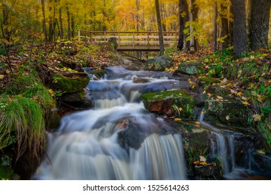 Small creek waterfall with a stream and bridge