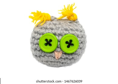 Small crocheted (knitted) owl toy of gray threads with yellow ears, a pink nose and eyes of green buttons isolated on a white background without shadow