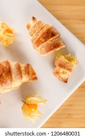 Small croissant with physalis fruits in white ceramic tray, homemade cakes on wooden table top.