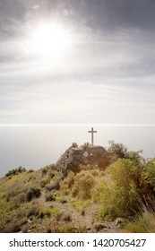 small cross on mountain side looking out to sea