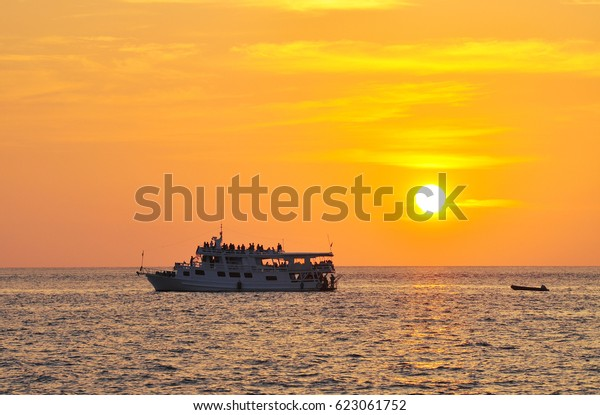 Small cruise ship travel in the ocean with sunset
