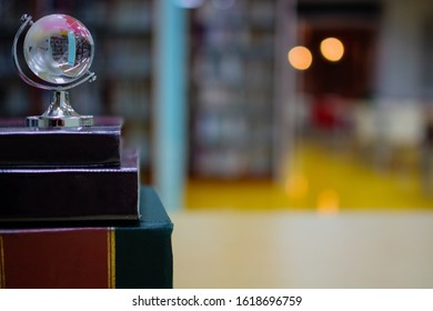 A small crystal globe upon stack pile of old books in academic library referred to achievement in studying, with blurred background of bookshelves and reading area. For learning concept. Copy space.