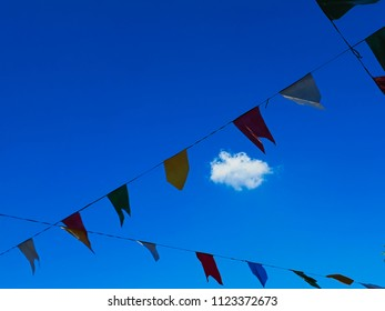 small cumulus cloud of white color under a blue sky, surrounded by small flags decorating a party kermesse junina, sao paulo, brazil