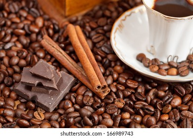 small cup of coffee and roasted coffee beans with retro wooden manual mill, cinnamon, chocolate bars close up