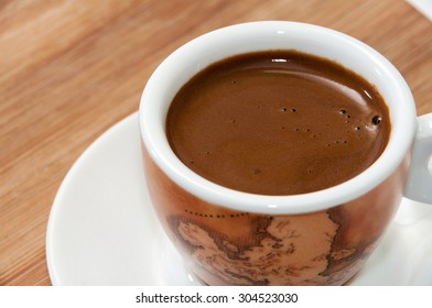 Small cup of coffee served on wooden board.