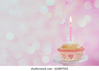 Small cupcake with a one burning striped candle on a pink background