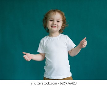 Small curly redheaded boy in a white t-shirt showing thumbs up,  ok sign