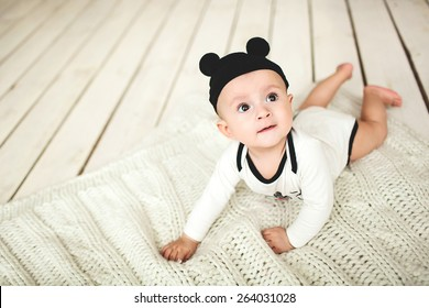 Small cute baby boy in toddler and mouse hat on rustic wooden floor