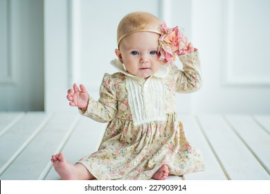 small cute baby girl with a adorable flower in fer head and in beautiful dress