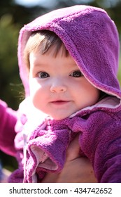 Small cute baby girl with pretty smiling face and funny eyes in hood sunny day outdoor on natural background closeup