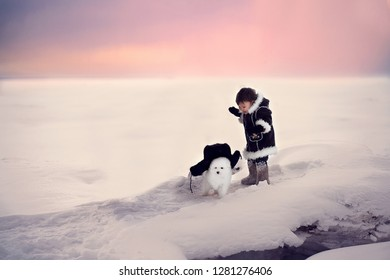 Small cute boy in earflaps is walking with his friend - little samoyed who looks like white bear. Image with selective focus and toning