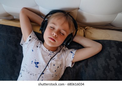 small cute boy seats on the bed and listening music with earphones and have rest and relax