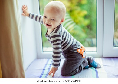 small and cute boy sitting on the windowsill and smiling