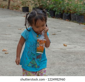 a small cute child walking and sipping a drink, taken at Pathumthani, Thailand, in April 2017.