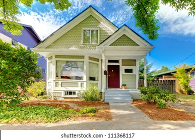 Small cute craftsman American house with green and white and red door.