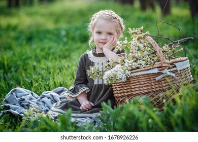 small cute girl in dress in blossom garden. Cute baby girl 3-4 year old holding flowers over nature background. Spring portrait. Aromatic blossom and retro vintage concept.