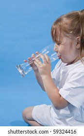 Small cute girl is drinking water on blue background.