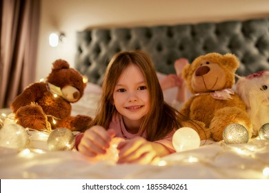 A small cute girl is lying alone on her stomack on a big bed barefoot having a good time looking into a camera, smiling and having her teddybears and garlands around her in a spacy bedroom