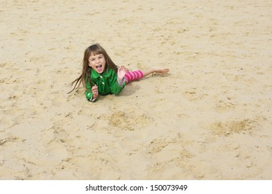 Small cute girl lying on sand at beach.