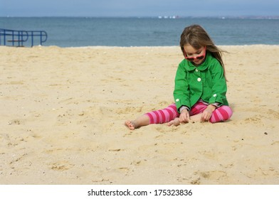 Small cute girl playing on sand at beach.