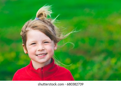small cute girl portrait. adorable blond kid close up. cheerful preschooler enjoying vacation outside on windy day.