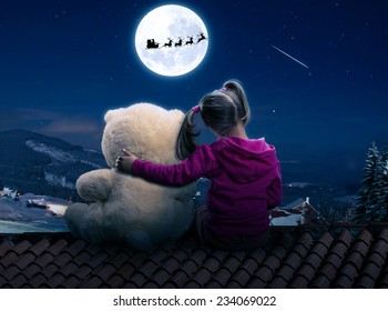 Small cute girl sitting on the roof with toy bear