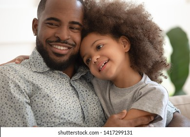Small cute mixed race kid daughter embrace loving black dad smiling bonding sit on sofa, happy affectionate african american family single father and little child girl hugging enjoy moments of love