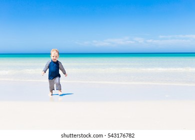 small cute toddler in swimsuit and sun protection having fun and running in shallow water on paradise summer destination, beach with blue ocean and white sand