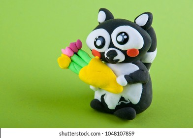 Small cute toy raccon made of modelling clay holding flower bouquet on green background