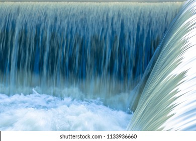 Small dam with water flowing rapids. Seen as lines and patterns with foam.